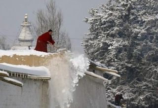 Buddhist Monk Shoveling Snow
